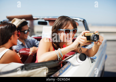 Smiling woman taking picture from convertible - Stock Photo