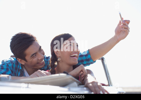 Smiling couple taking picture of themselves - Stock Photo
