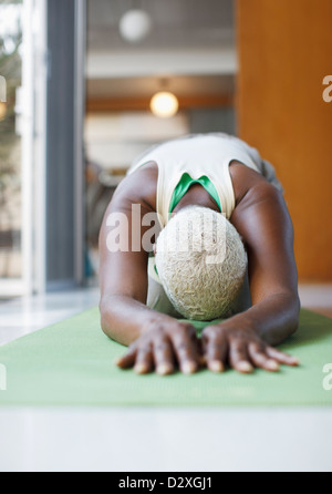 Older woman practicing yoga in living room - Stock Photo
