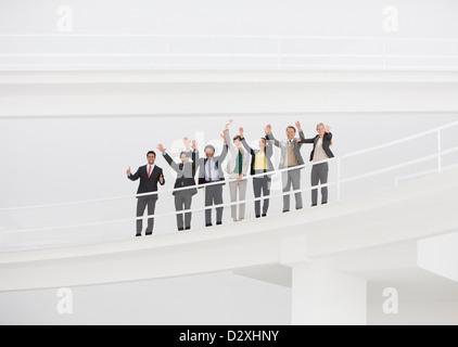 Portrait of cheering business people on elevated walkway - Stock Photo