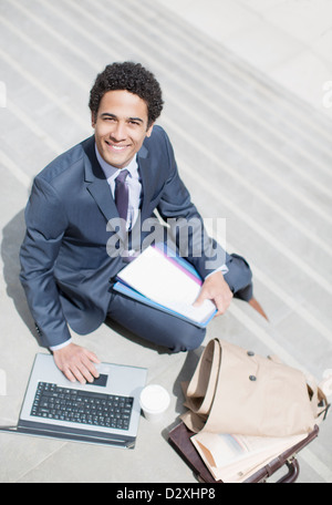 Portrait of smiling businessman with paperwork using laptop on sunny stairs - Stock Photo