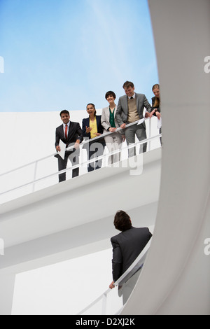 Businessman looking up at business people on elevated walkway - Stock Photo