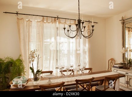 Chandelier over dining room table - Stock Photo