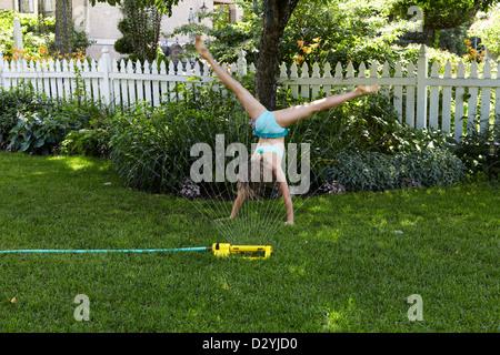 9 year old girl doing cartwheel on lawn - Stock Photo