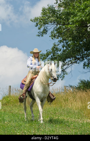 Woman horseback riding on beautiful white horse outdoors in nature and sunshine, a cowgirl in American western style - Stock Photo