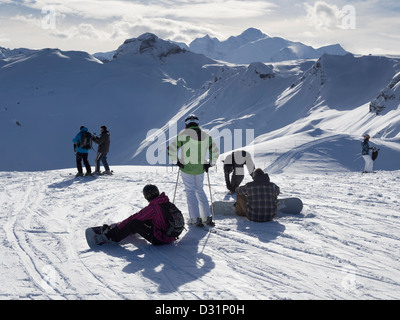 Skiers and snowboarders on piste in Le Grand Massif ski area with a view to Mont Blanc in French Alps. Grands Vans - Stock Photo