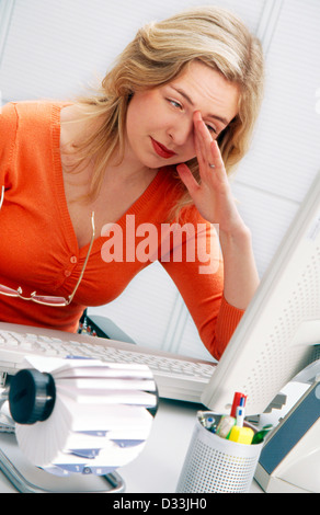Young office employee rubbing her eyes - Stock Photo