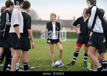 A girl joins a group of boys for a game of football at Pates Grammar School in Cheltenham, Gloucestershire UK - Stock Photo