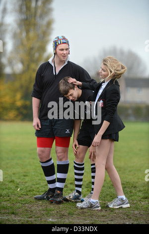 A girl joins a group of boys for a game of rugby at Pates Grammar School in Cheltenham, Gloucestershire UK - Stock Photo