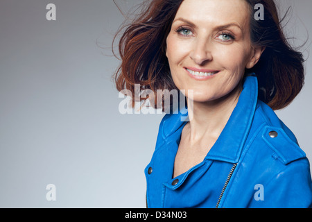 Attractive happy middle-aged woman in blue jacket.  - Stock Photo