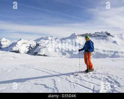 Male skier skiing in Le Grand Massif ski area with views to snowcapped mountains in the French Alps. Flaine, Rhone - Stock Photo
