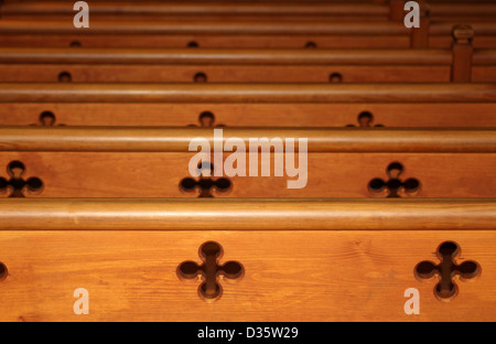 Row of wooden pews receding in church - Stock Photo