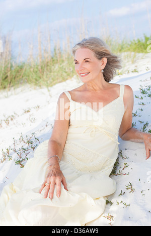 Happy senior woman looking out to sea on a deserted tropical beach with bright clear blue sky laying in the sand - Stock Photo