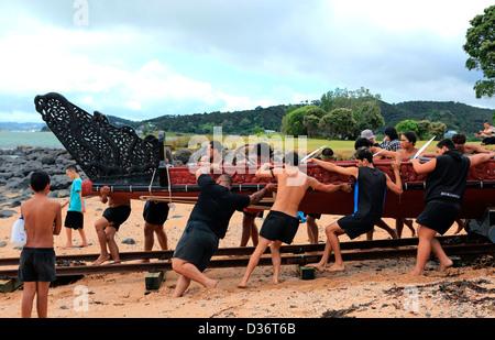 Maori waka crew with the great waka Ngatokimatawhaorua at the Waitangi Treaty Grounds during Waitangi Day celebrations. - Stock Photo