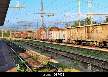 Old rusty freight cars stand on the track at the railway station. - Stock Photo