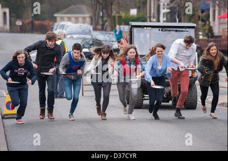 Competitors (male & female teenagers) with frying pans, taking part, running & racing in traditional Pancake Race - Stock Photo