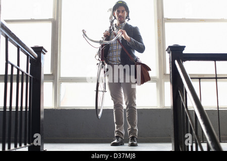 Man carrying bicycle on staircase - Stock Photo