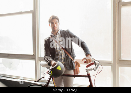 Man standing with bicycle by window - Stock Photo