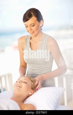 Woman giving scalp massage outdoors - Stock Photo