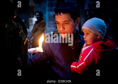Jerusalem, Israel. 13th February 2013. A man holds a candle and his infant child by the Edicule of the Tomb in the - Stock Photo
