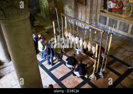 Jerusalem, Israel. 13th February 2013. Christian devotees kneel before the Stone of Unction, also known as the Stone - Stock Photo