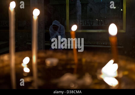 Jerusalem, Israel. 13th February 2013. A woman prays silently in the Church of the Holy Sepulchre on Ash Wednesday. - Stock Photo