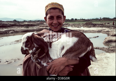 Afghan refugee boy with a young goat. Refugee Camp. Peshawar, Pakistan - Stock Photo