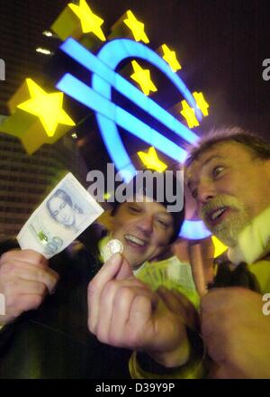 (dpa) - Two men inspect the new Euro money compared to the good old German Mark (l) standing next to the giant Euro - Stock Photo