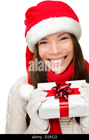 Joyful mixed race Asian Caucasian woman wearing Santa hat showing Christmas present isolated on white background - Stock Photo