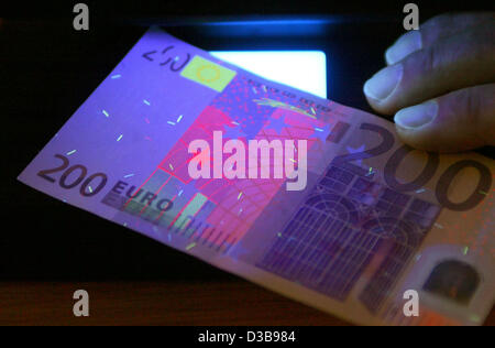 (dpa file) - The picture dated 30 November 2004 shows a counterfeited 200-euro bill under an ultraviolet lamp at - Stock Photo