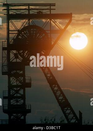 (dpa files) - The sun goes down behind a winding tower of the colliery 'Zollverein' (German Customs Union) in the - Stock Photo