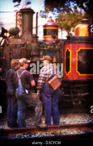 A vintage old style photo of a group of engine drivers and railway workers standing beside an old working steam - Stock Photo