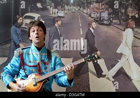 (dpa) - Paul McCartney impersonator Freddie May plays the guitar in front of an enlarged album cover of the Beatles - Stock Photo