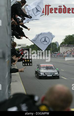 (dpa) - Fans cheer as the British DTM pilot Gary Paffett steers his AMG-Mercedes C class towards to finishing line - Stock Photo