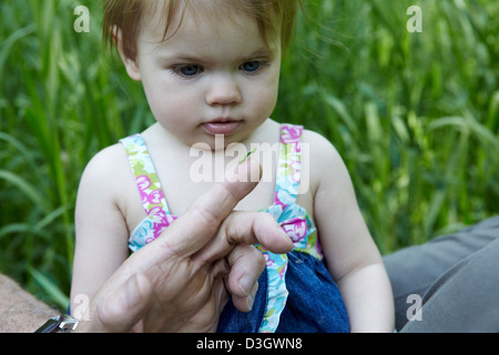 1 year old girl looks at green caterpillar - Stock Photo
