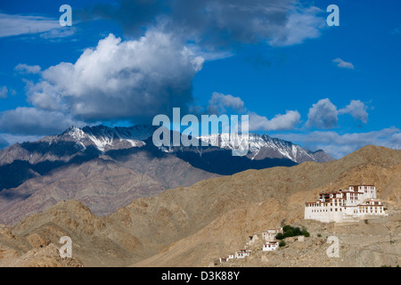 Chemrey Gompa dwarfed by rugged snow-capped mountains and stormy clouds, (Ladakh) Jammu & Kashmir, India - Stock Photo