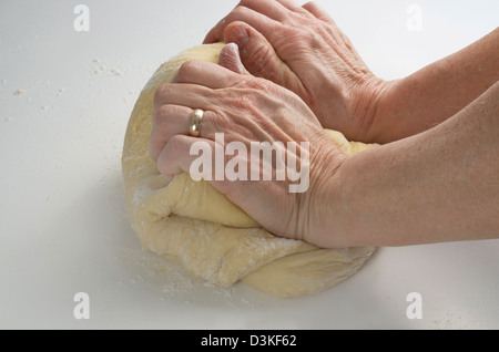 Two hands kneading bread dough on a white surface. - Stock Photo