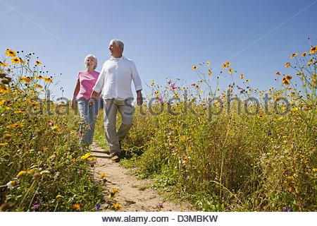 Smiling senior couple walking on path through wildflower meadow - Stock Photo