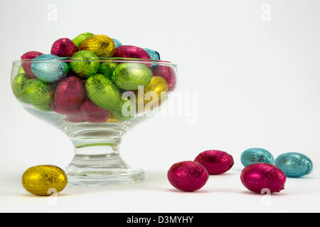 Brightly coloured Easter Eggs in a glass bowl. - Stock Photo