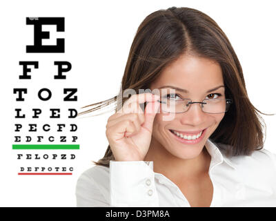 Smiling Caucasian / Asian Chinese woman wearing glasses standing by Snellen eye exam chart isolated on white background - Stock Photo