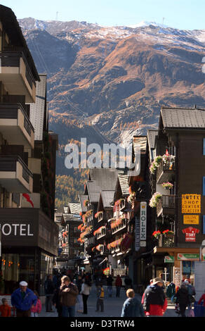 The photo shows visitors in the mountain town Zermatt in front of the surrounding hills in the Swisss canton Wallis, - Stock Photo