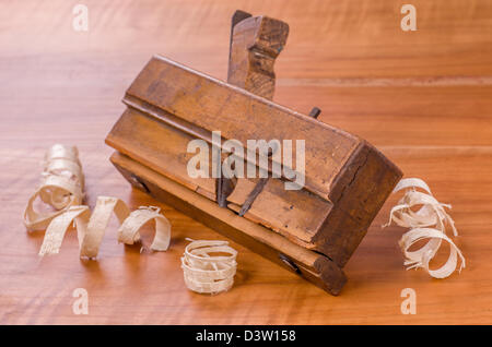 old molding plane with shavings on a cherry wood board - Stock Photo