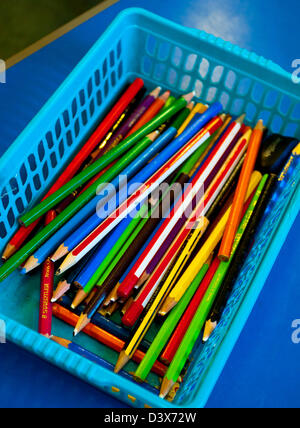 Close up view of colourful pencils in a plastic basket in a school classroom - Stock Photo
