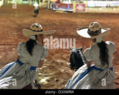 Mexico, Jalisco,Guadalajara, Mexican charras, female cowgirls on horseback at rodeo - Stock Photo