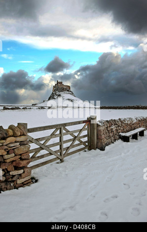 Lindisfarne Castle Holy Island, Northumberland sunset sky brooding clouds Snow dry Stone wall with wooden gate leads - Stock Photo