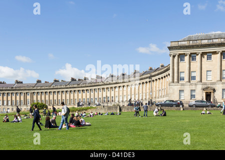 Visitors relax on the lawn near the Royal Crescent, Bath, the curved terrace of townhouses designed by John Wood - Stock Photo