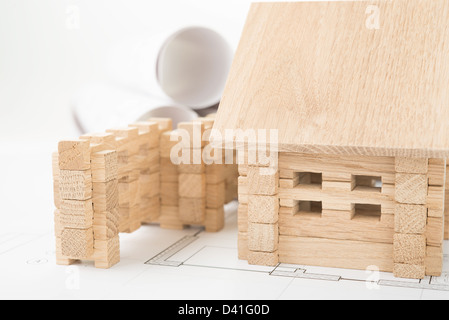 wooden house on an architectural plans and blueprints - Stock Photo
