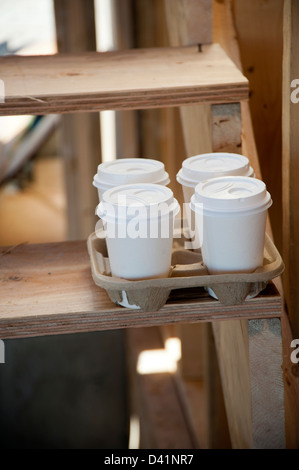 Four styrofoam take away coffee cups sitting on ladder in construction zone - Stock Photo