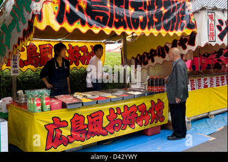 Roten stand is selling famous Hiroshima okonomiyaki, a Japanese pizza with cabbage, meat and eggs, at a festival - Stock Photo