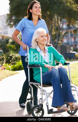 Carer Pushing Senior Woman In Wheelchair - Stock Photo